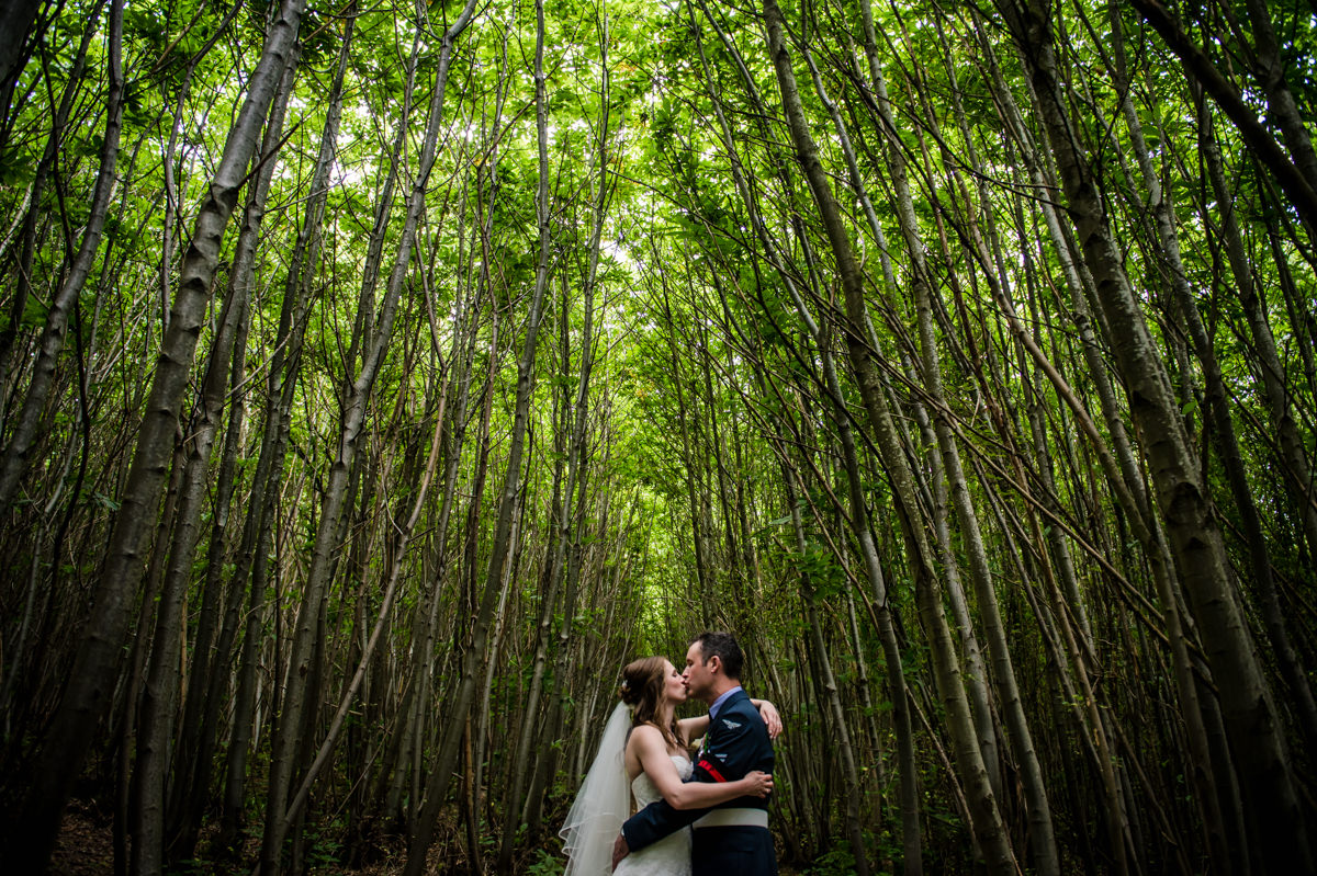 newly married couple kissing in woods