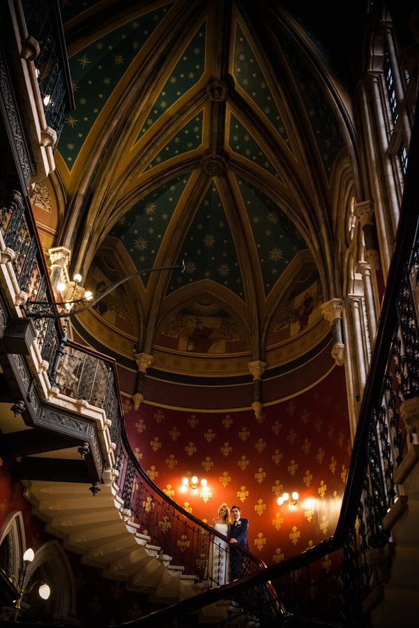 newly weds standing on stair case at St Pancras Renaissance Hotel