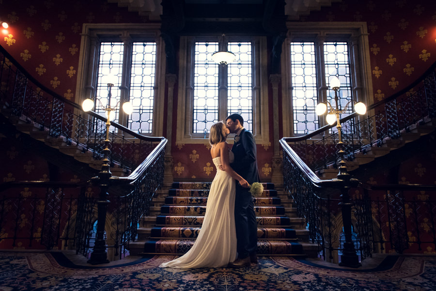 elegant photo of bride and groom kissing on the staircase at St Pancras Renaissance Hotel