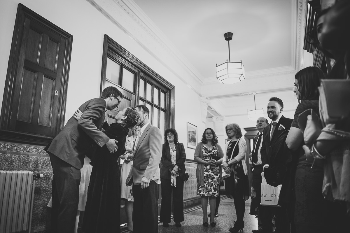 Newly weds greeting and hugging guests at their croydon registry office wedding