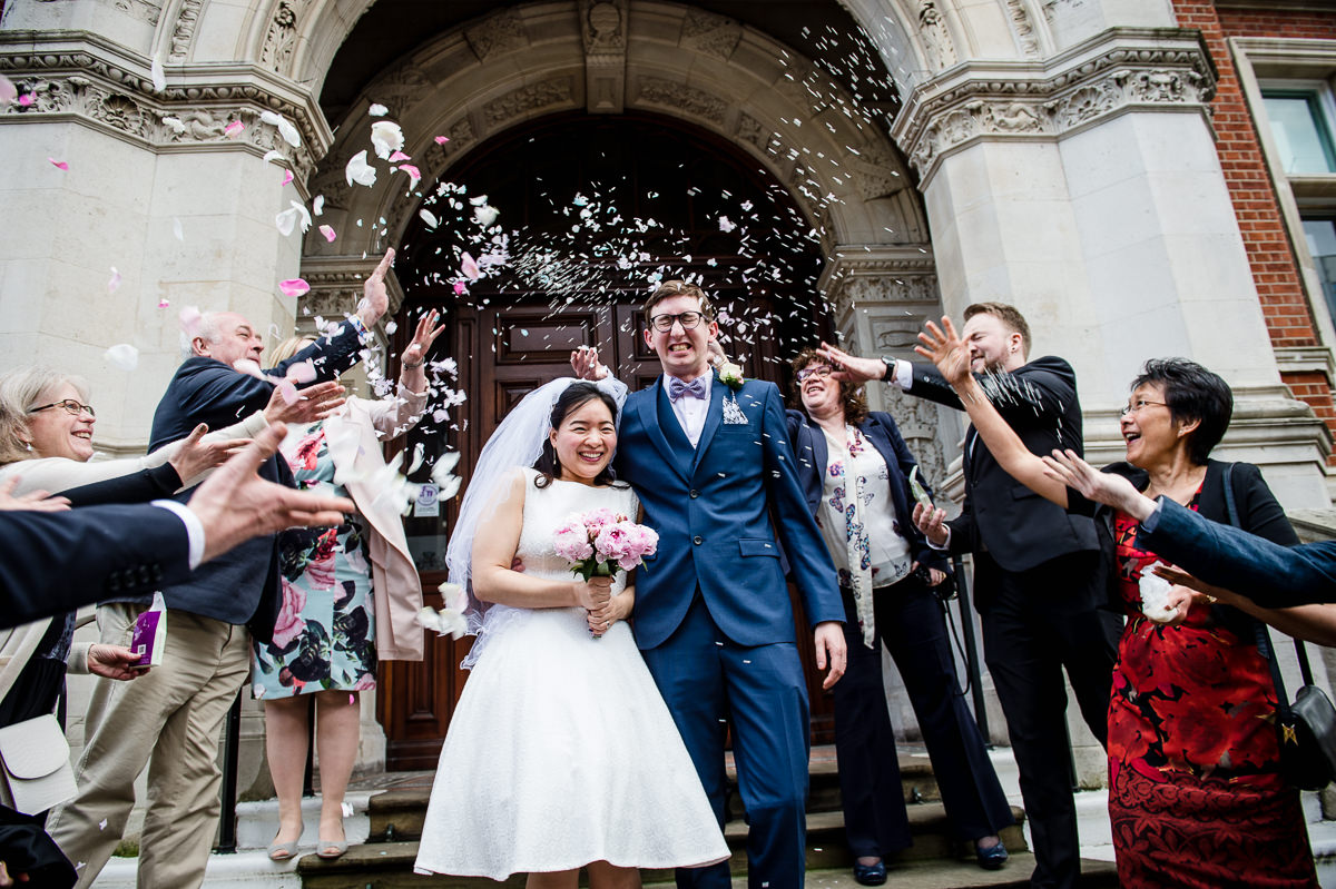 Bride & Groom being covered in confetti on the steps of Croydon Old Town hall