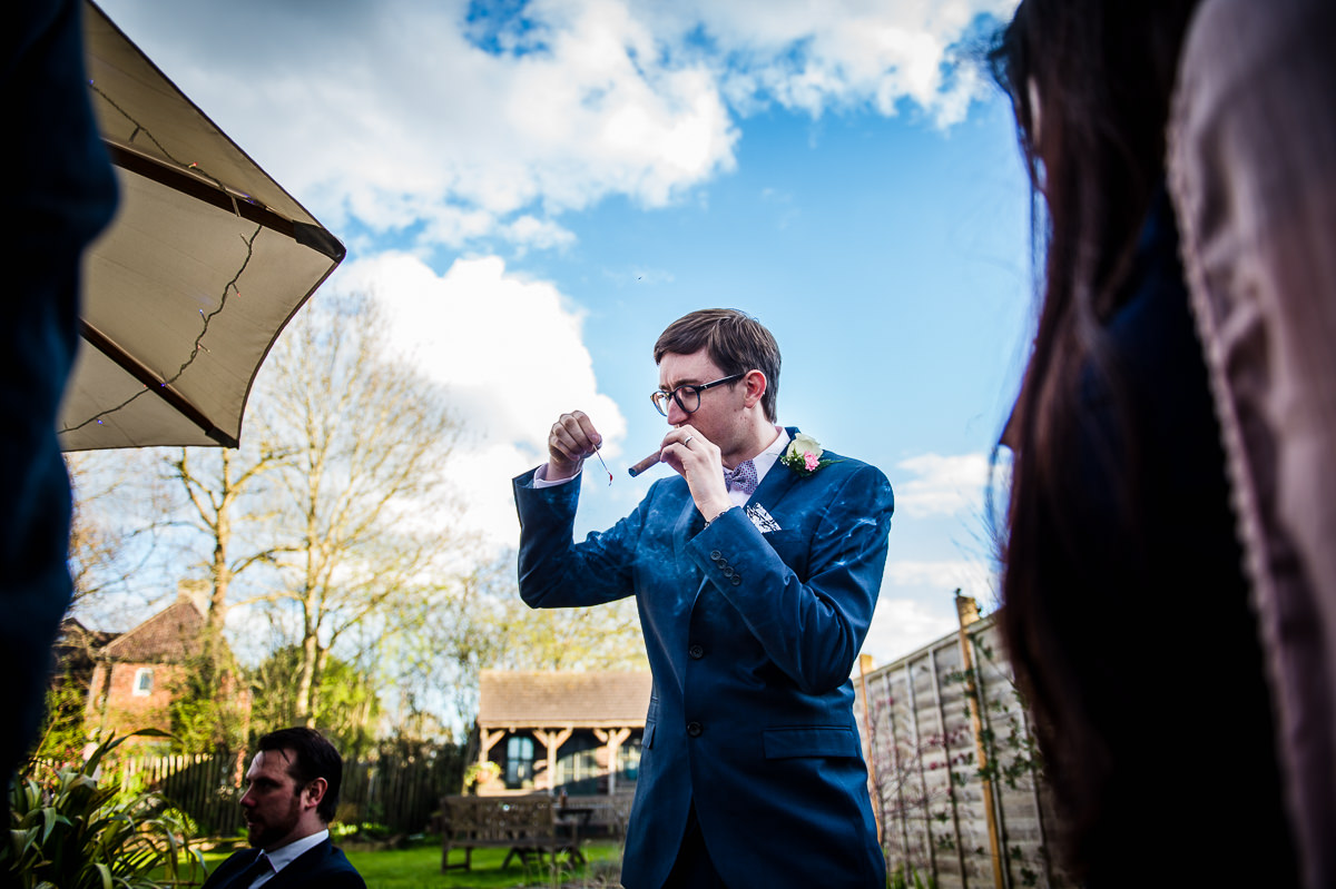 Groom smoking a cigar at his relaxed surrey garden wedding