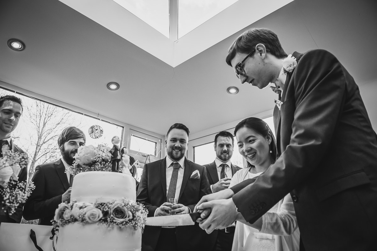Bride and Groom curling their wedding cake at their surrey garden wedding