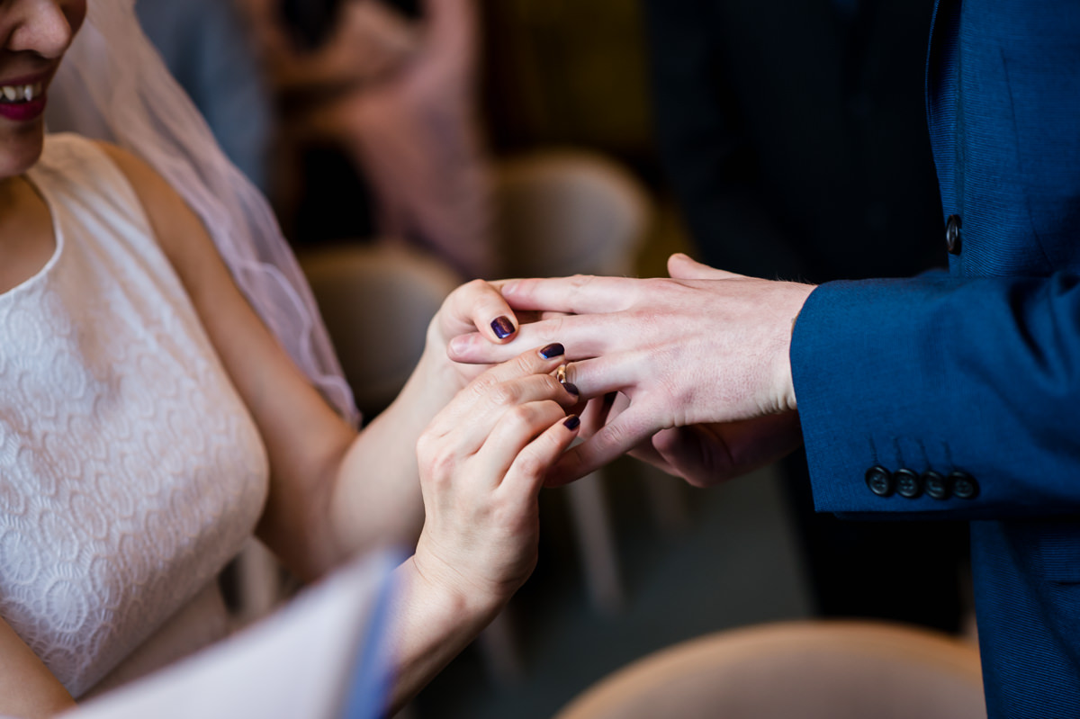 Bride placing wedding ring on Groom's finger during their wedding