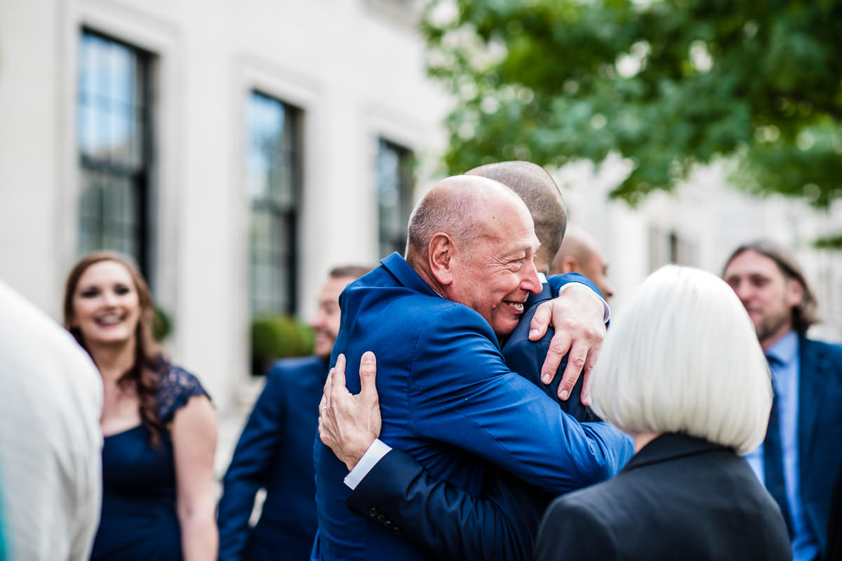 Town Hall Hotel wedding groom hugging father in law