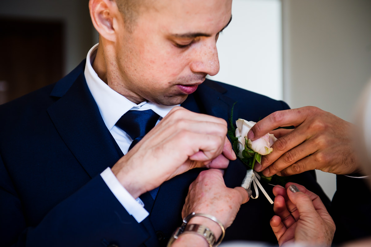 Bethnal Green Town Hall Hotel wedding groom putting on button hole