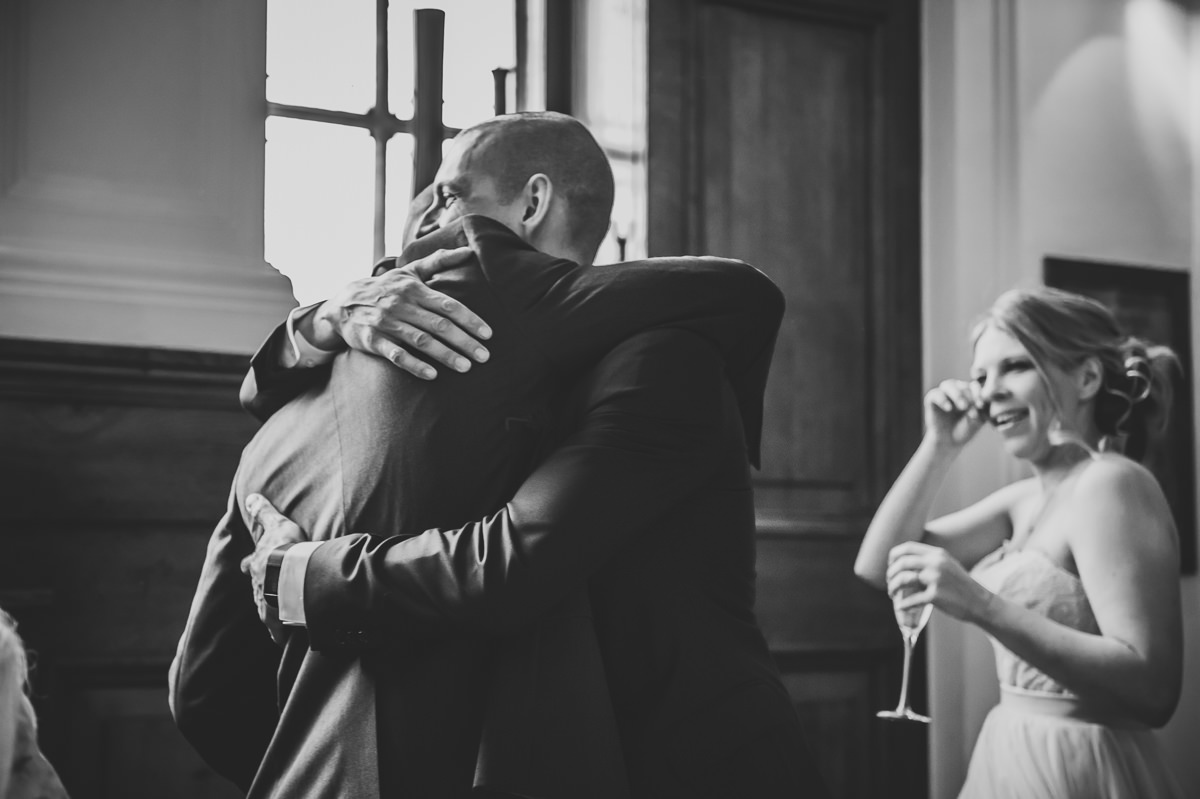 Groom and Best Man hugging at Town Hall Hotel wedding