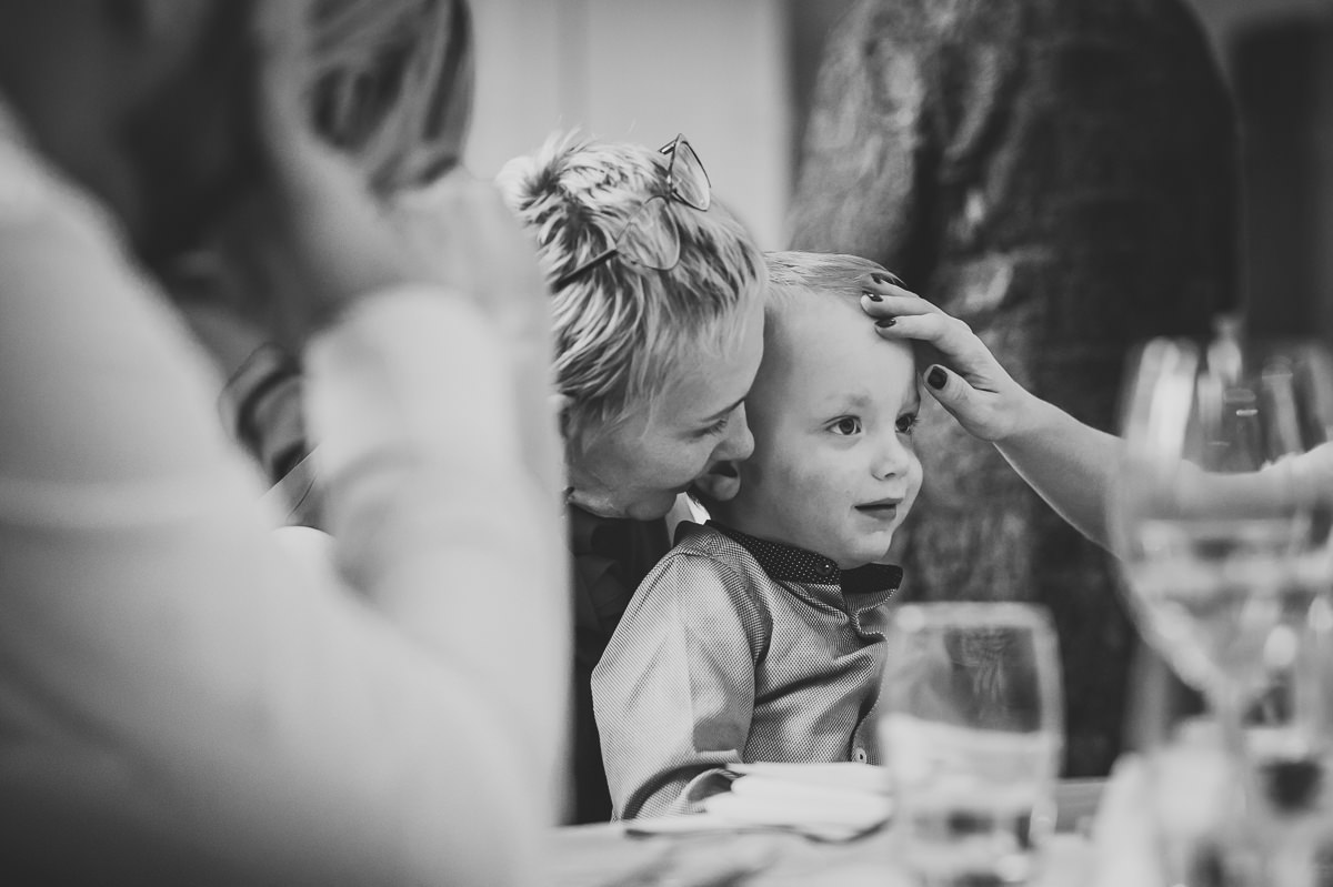 Mother touching her young son's face at wedding
