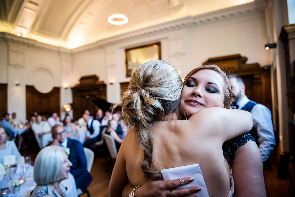 Bridesmaid hugging Bride after giving speech