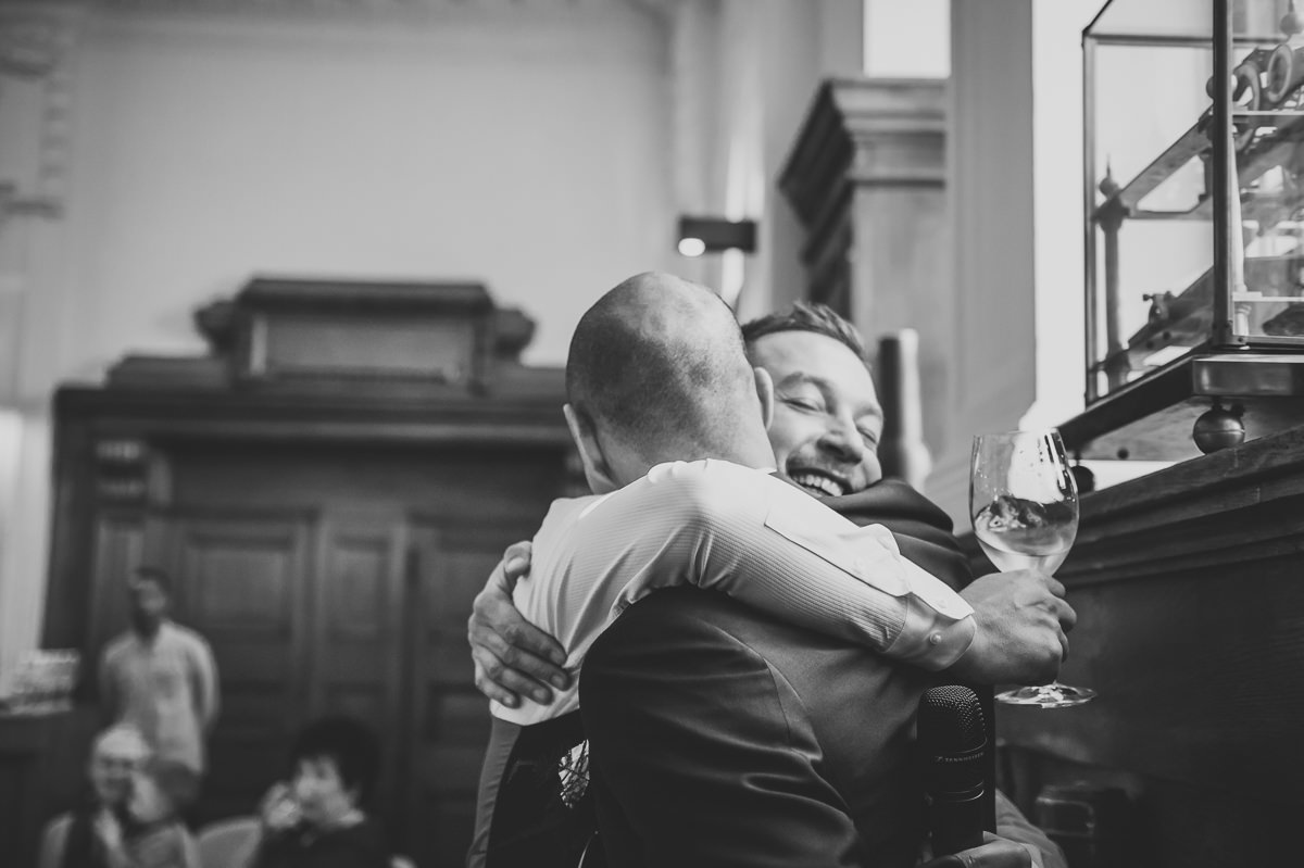 Brides brother hugging Groom at this wedding
