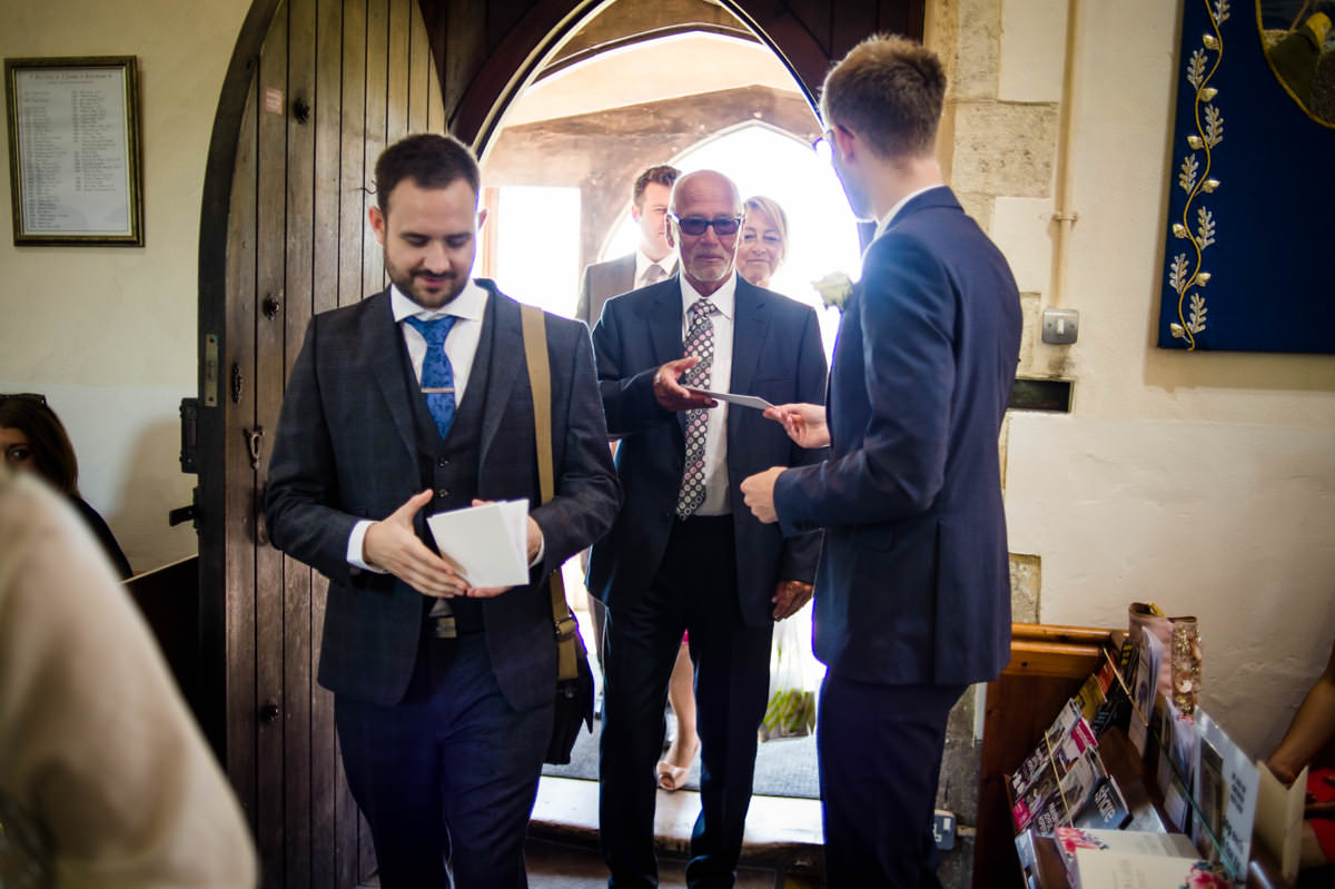 groomsmen handing out orders of service before the wedding in west sussex