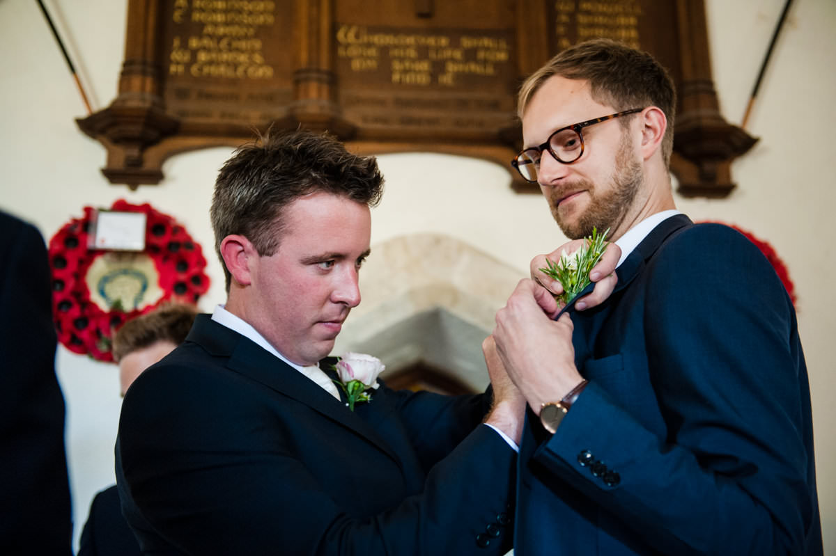 groom helping guest to put on wedding button hole