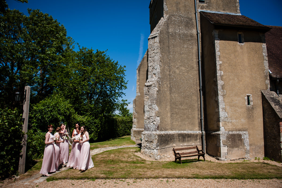 bridesmaids waiting outside of church in pretty pink dresses