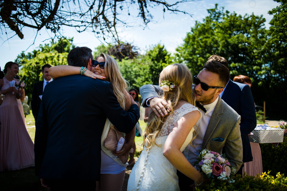 Bride and Groom hugging guests at their Sussex wedding