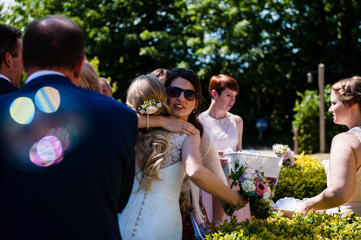 Bride hugging guests at her wedding