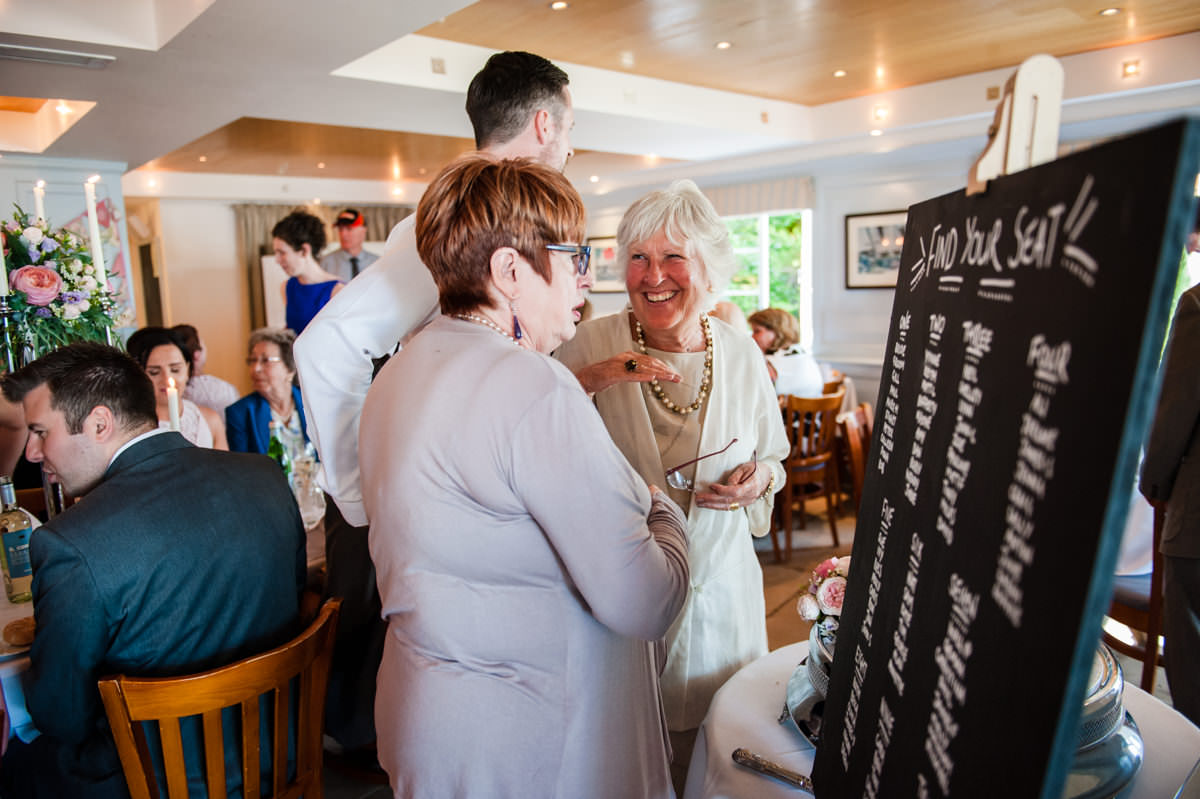 Guests looking at seating plan at Itchenor Sailing Club wedding