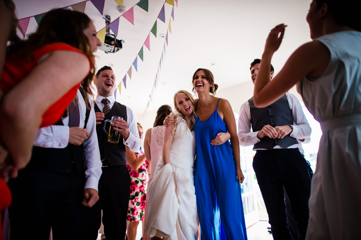 Bride surrounded by friends dancing at her Sussex wedding