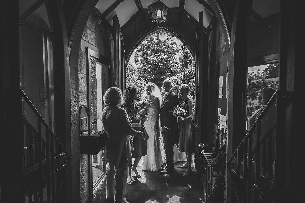 Bride waiting at the church door with her dad and bridesmaids, ready for the wedding