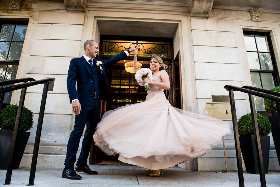 groom spins bride around in her pink dress