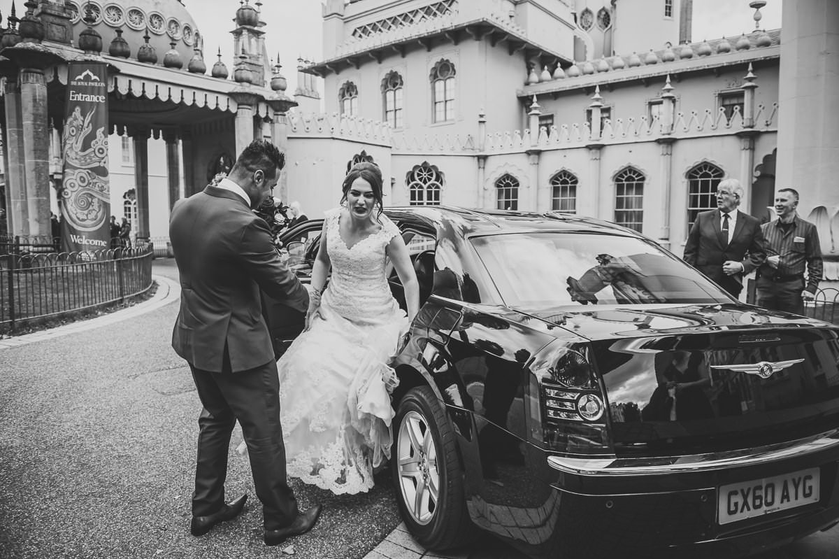 Handsome groom helps his beautiful bride out of their wedding car ready for their wedding ceremony at the pavilion