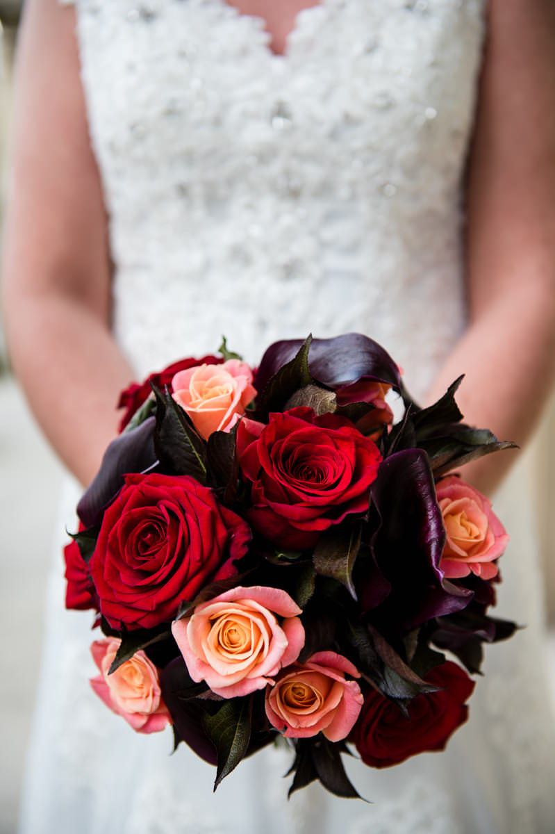 Bride's autumnal bouquet of red roses and cala lillies