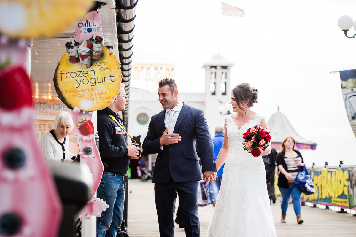 Newly weds on brighton pier after their wedding ceremony