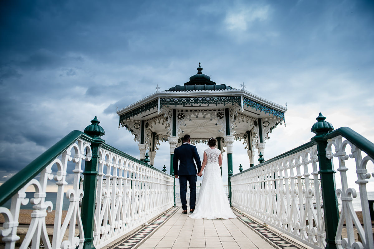 bride and groom walking onto brighton bandstand