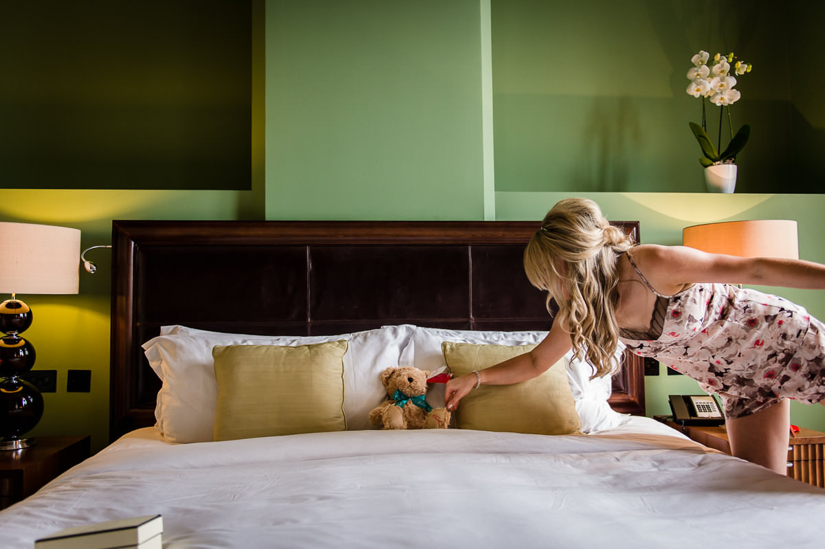 Bride placing her new Hamley's teddy bear on her bed, a gift from her husband to be