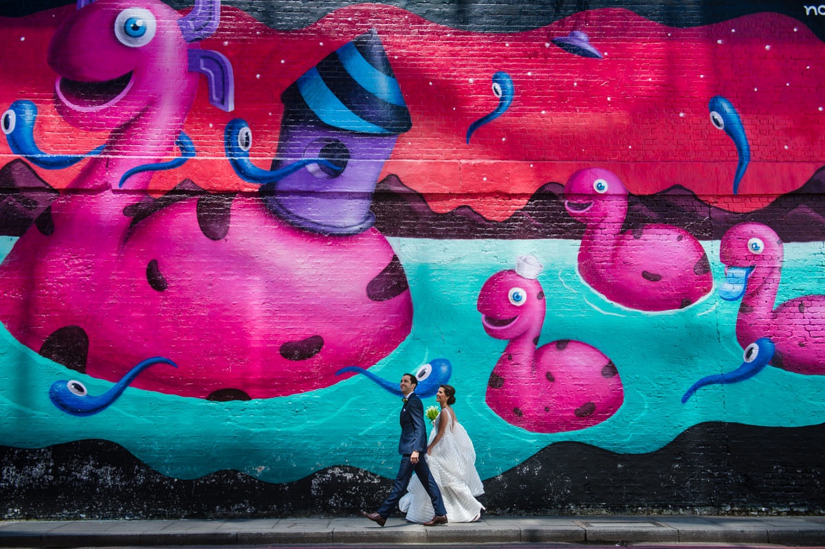 Colourful photo of bride and groom walking past a painted art wall in Shoreditch at their London wedding