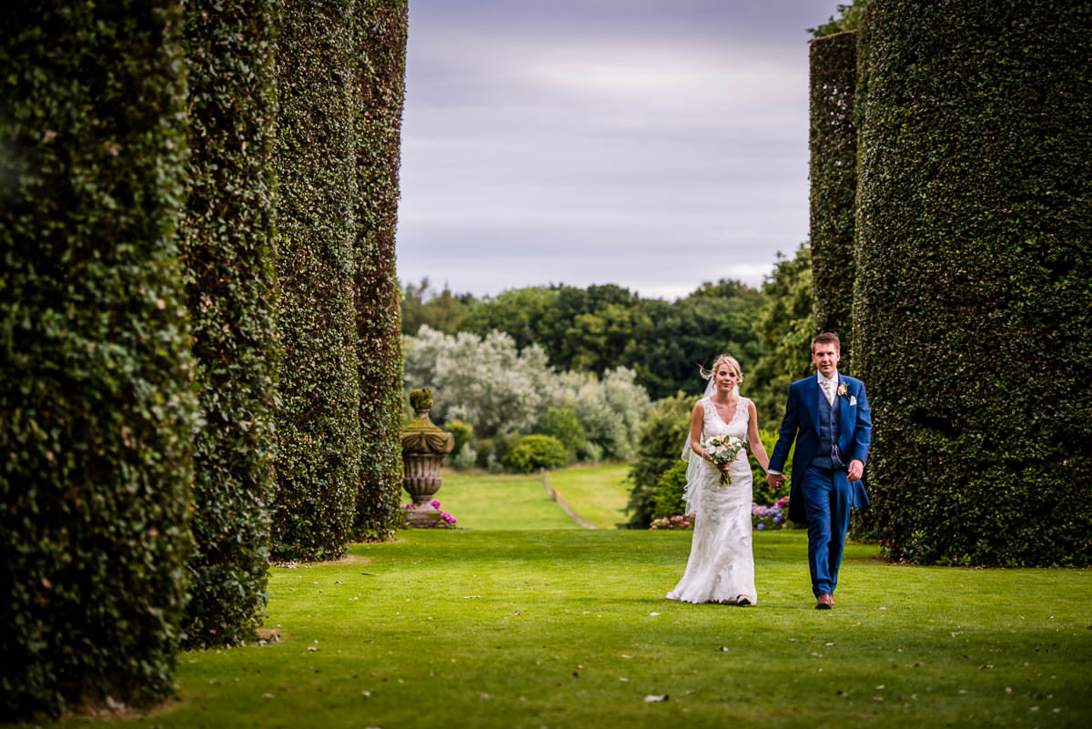 Bride & Groom walking through the stunning hedges in the gardens of Arley Hall
