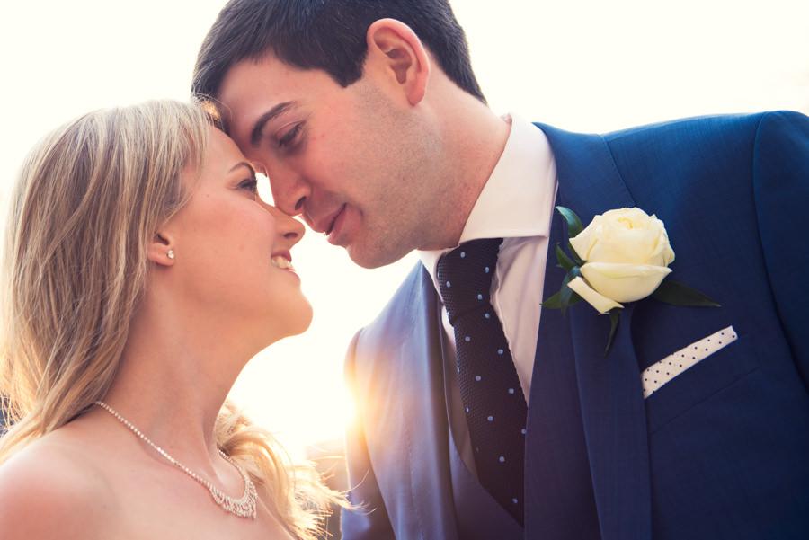 sunlight shining between bride and groom
