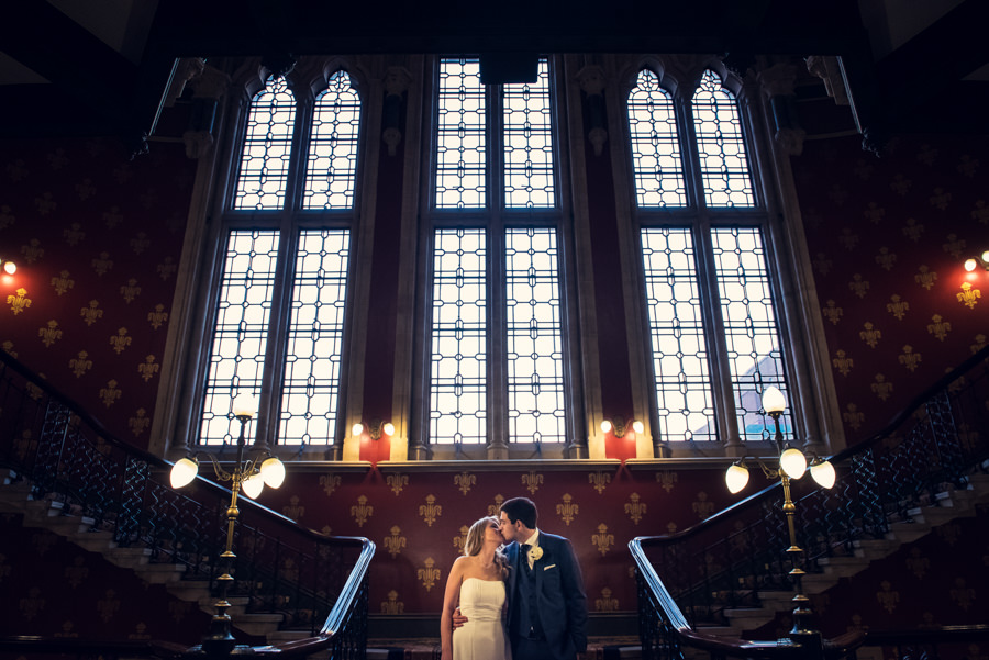 bride and groom kissing on staircase at St Pancras Renaissance Hotel
