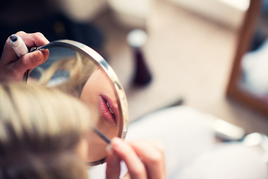 photo of brides lips reflected in mirror as she's getting ready for her wedding at Islington town hall