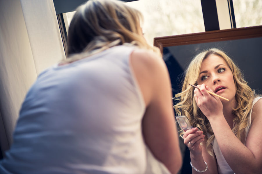bride putting her make up on as she's preparing for her wedding