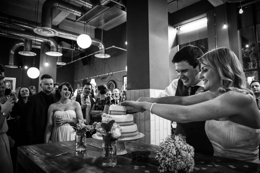 bride and groom cutting their cake at their the Artisan of Clerkenwell wedding reception