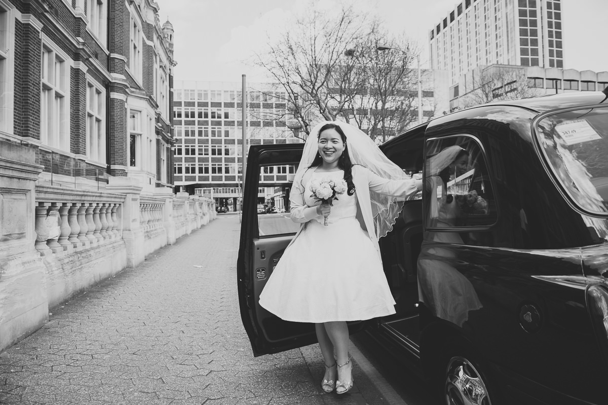 Spring Bride arrives at her croydon registry office wedding in black taxi