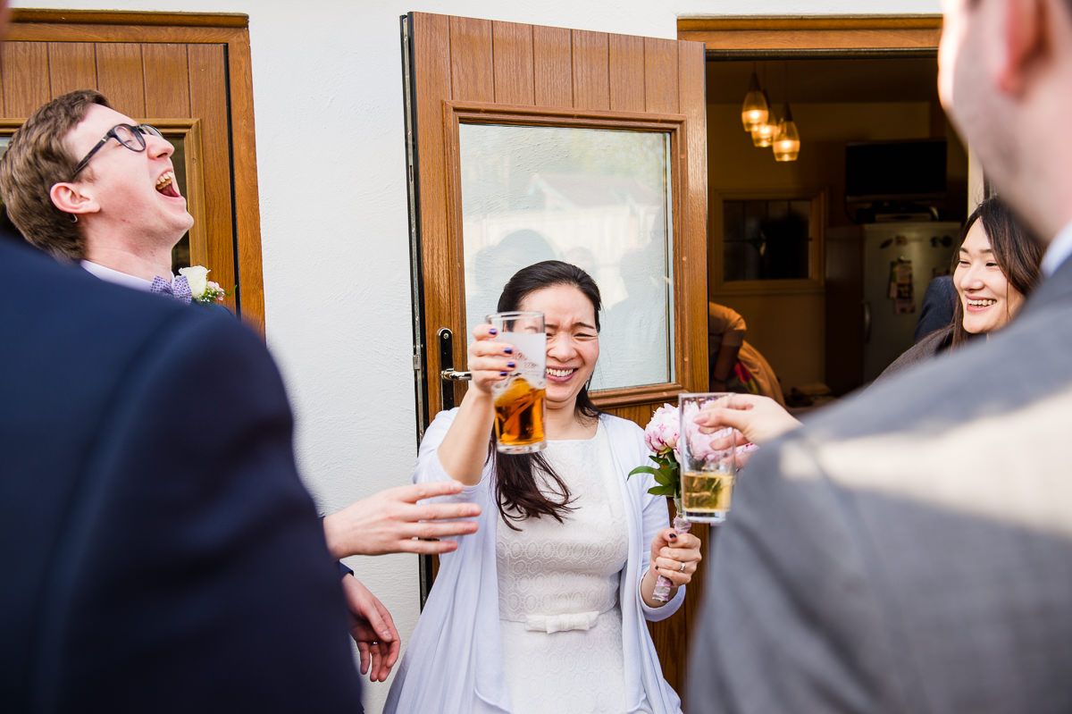 Bride and Groom clinking pints at their surrey garden wedding