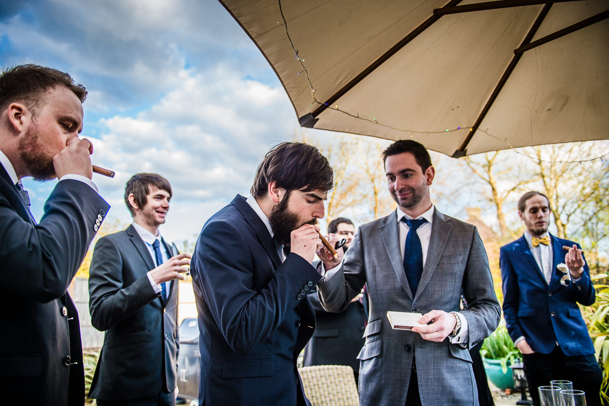 Guests relaxing and smoking cigars at a surrey garden wedding