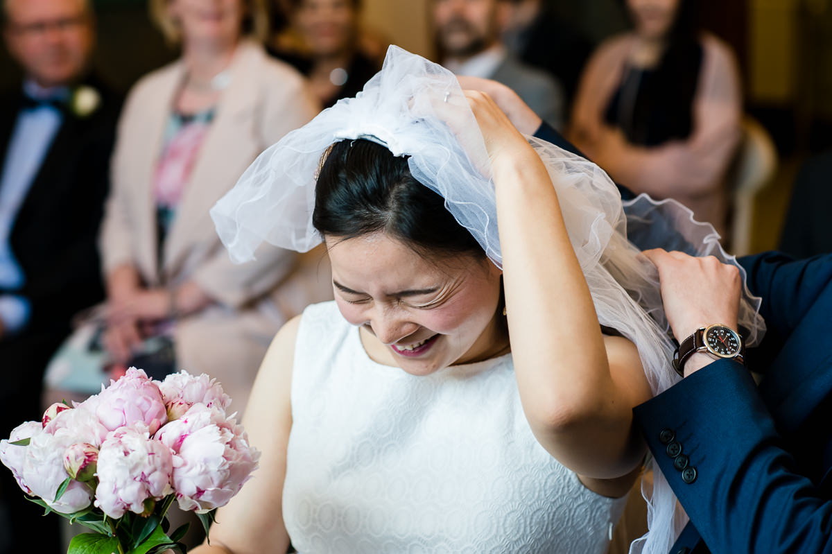 Bride laughing at her veil gets caught at her Croydon Registry office wedding