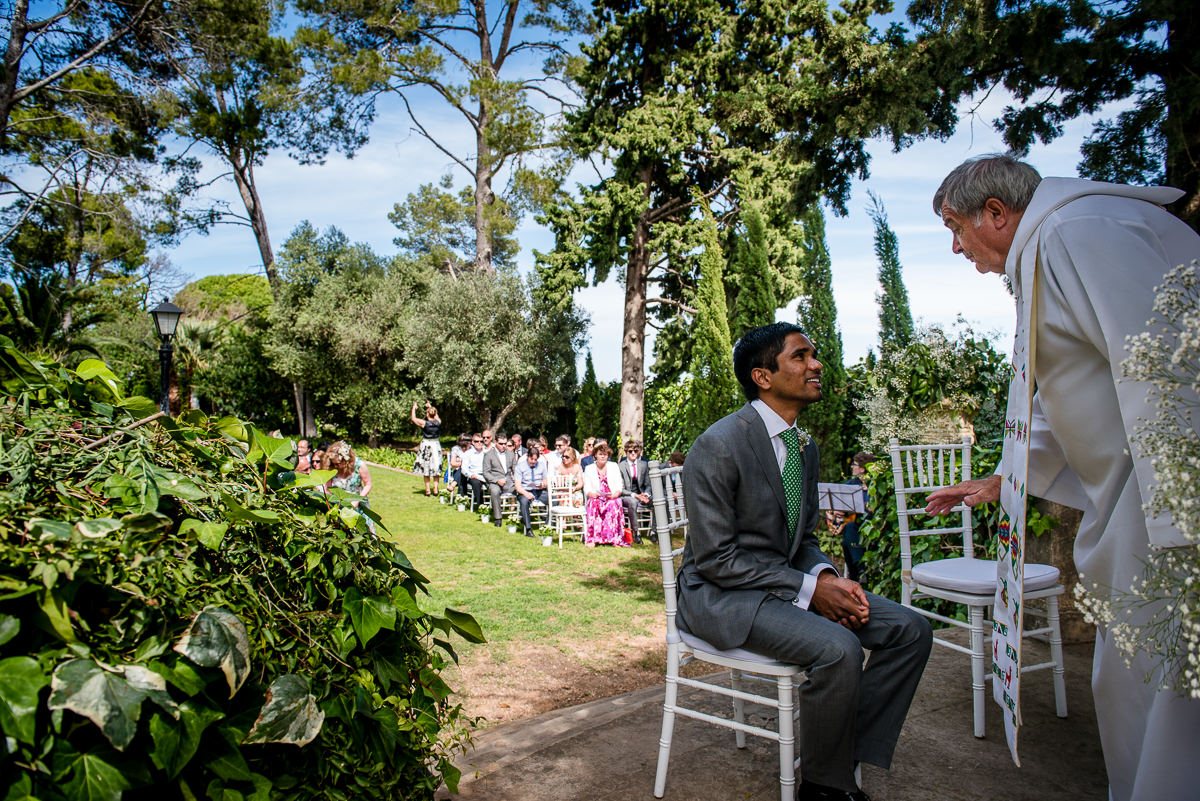 Groom waiting with guests for his bride at his outdoors Casa Santonja wedding