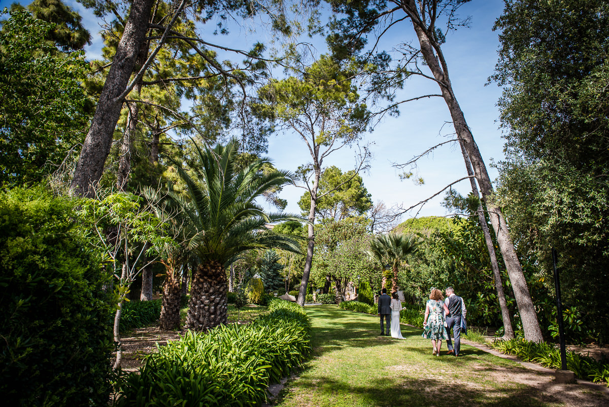 Newly weds and guests walking down the long garden aisle at Casa Santonja