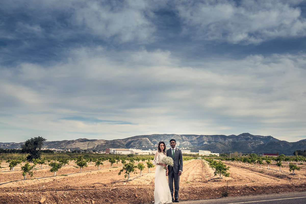 Newly married couple in front of casa santonja and the mountains