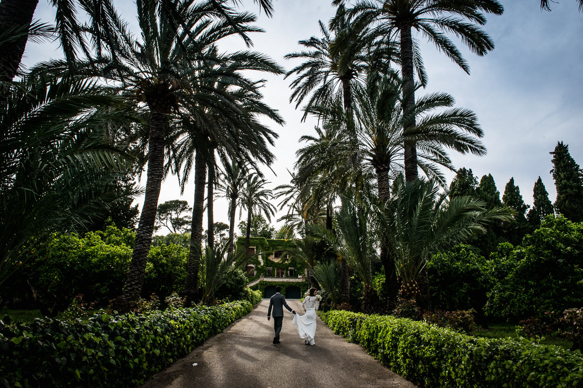 Palm trees at spanish destination wedding with bride and groom walking