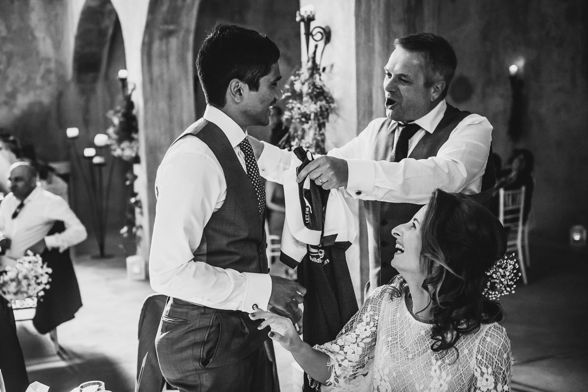 Father of bride giving groom a football shirt at his spanish wedding