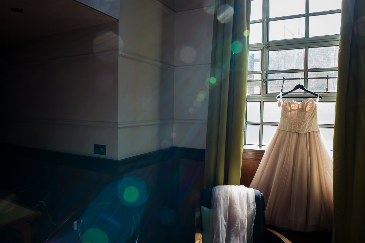 Bethnal Green Town Hall Hotel wedding brides dress hanging in window