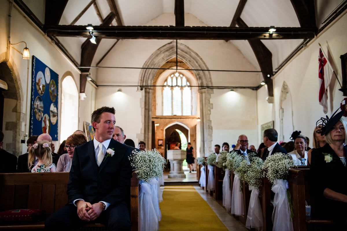 groom waiting at the top of the aisle for his bride to arrive