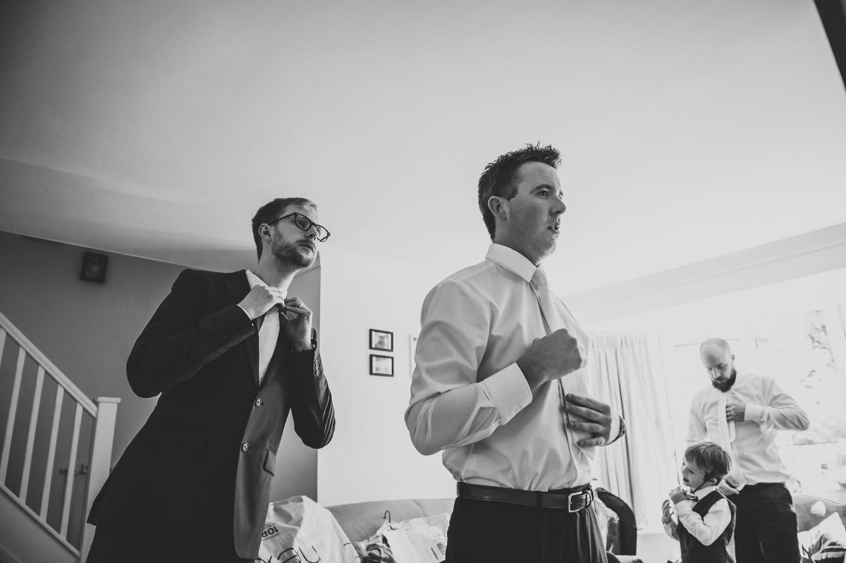 Groom and groomsmen doing up their ties for wedding