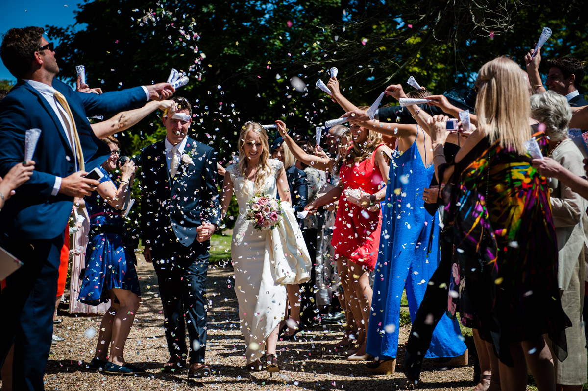 Bride and Groom walking through confetti shower after their west sussex wedding
