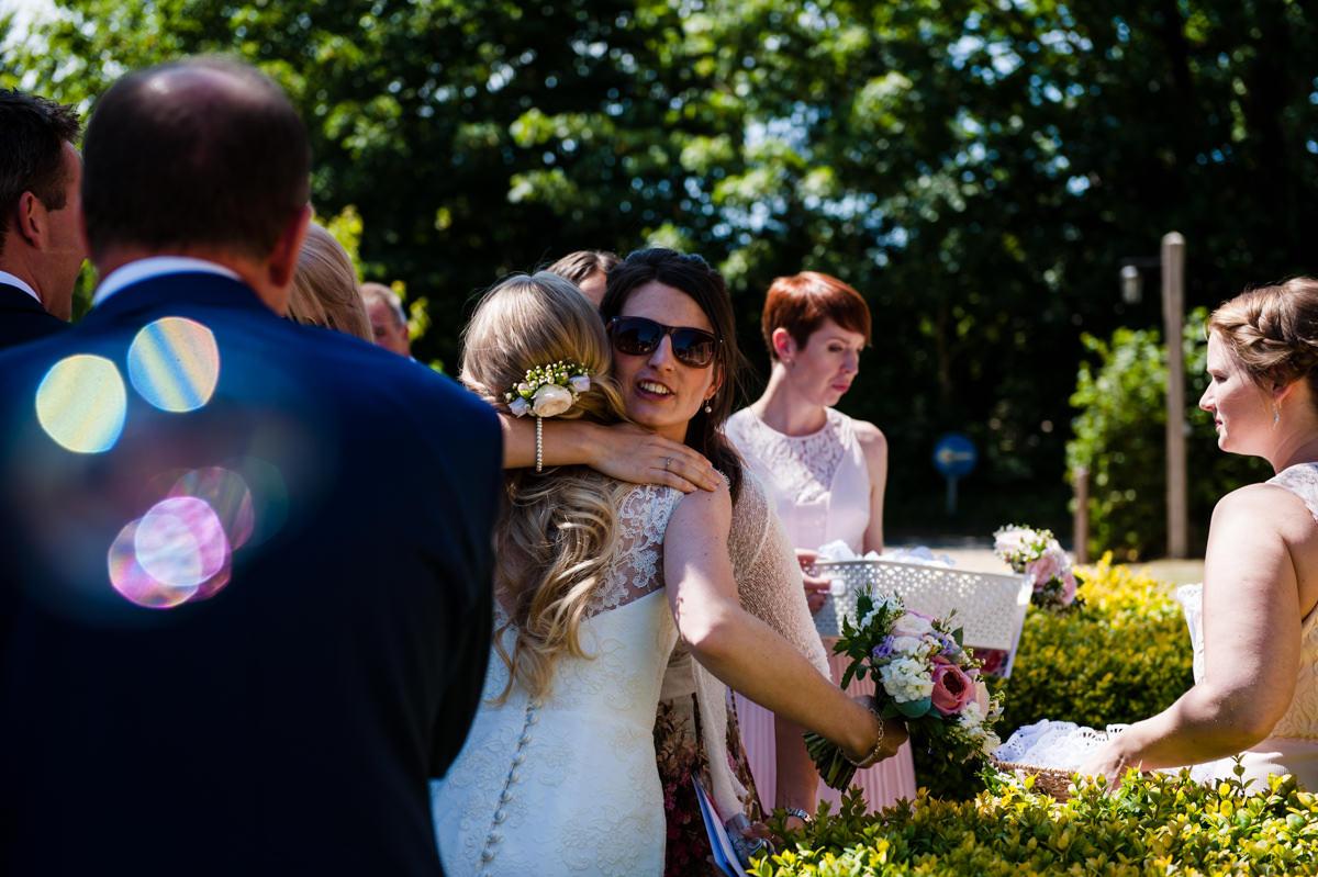Bride hugging guests at her wedding