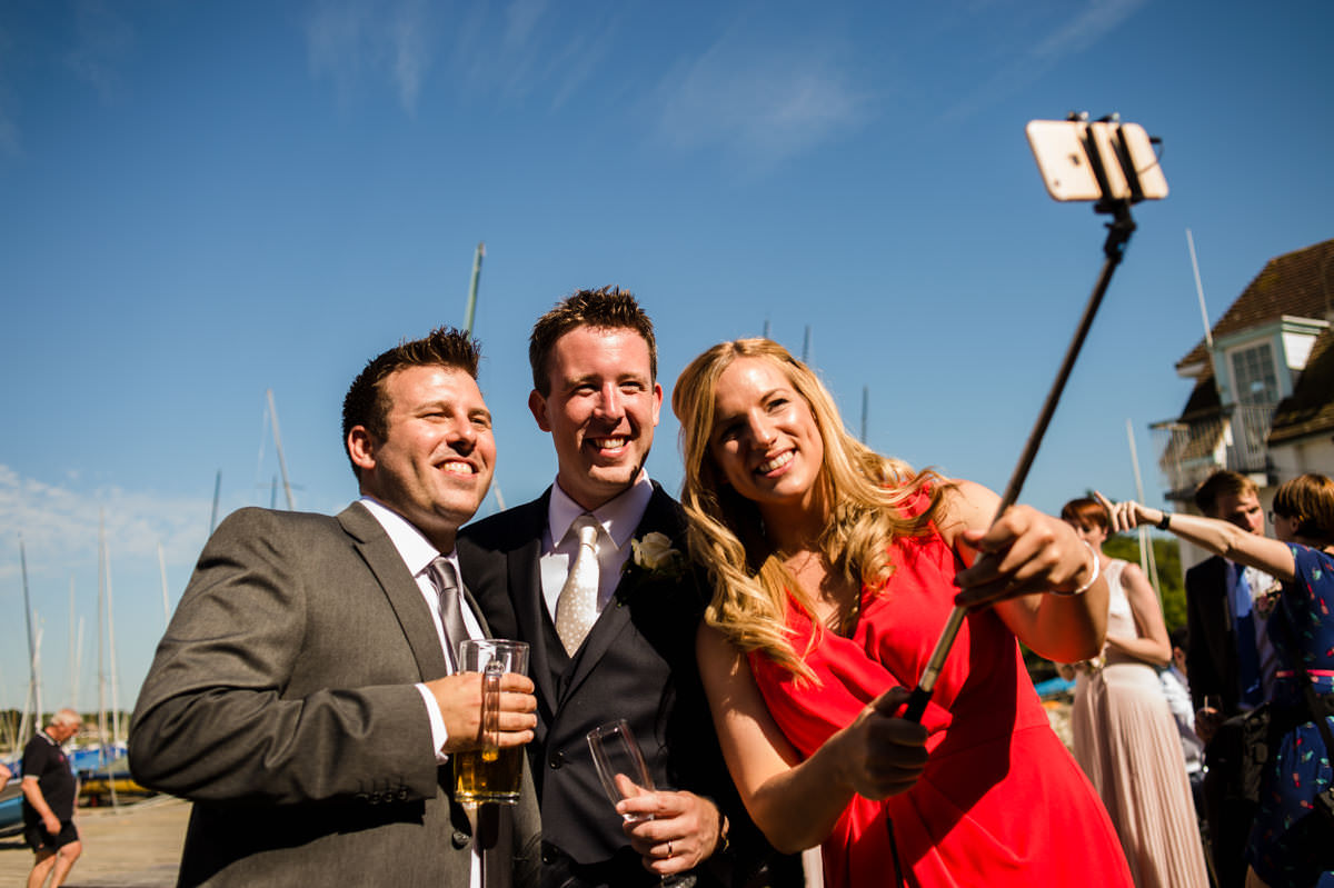 Groom and guests taking selfies at west sussex wedding